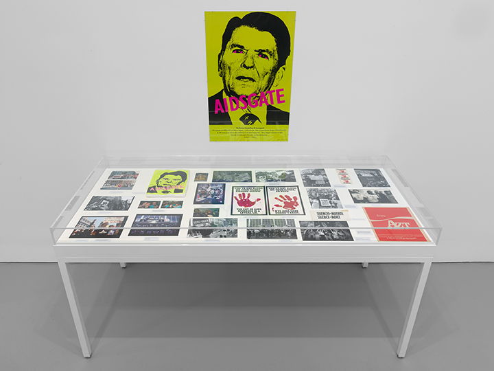 Protest ephemera, including a poster of Reagan toned green and superimposed with the word AIDSGATE, is displayed in a gallery.