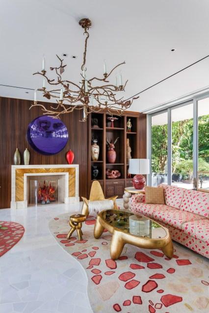 Une œuvre de l'artiste Anish Kapoor est accrochée au-dessus de la cheminée de style Art déco du salon. La pièce compte aussi un lustre de Claude Lalanne, suggérant un univers végétal, du mobilier en bois doré et un fauteuil de Wendell Castle.