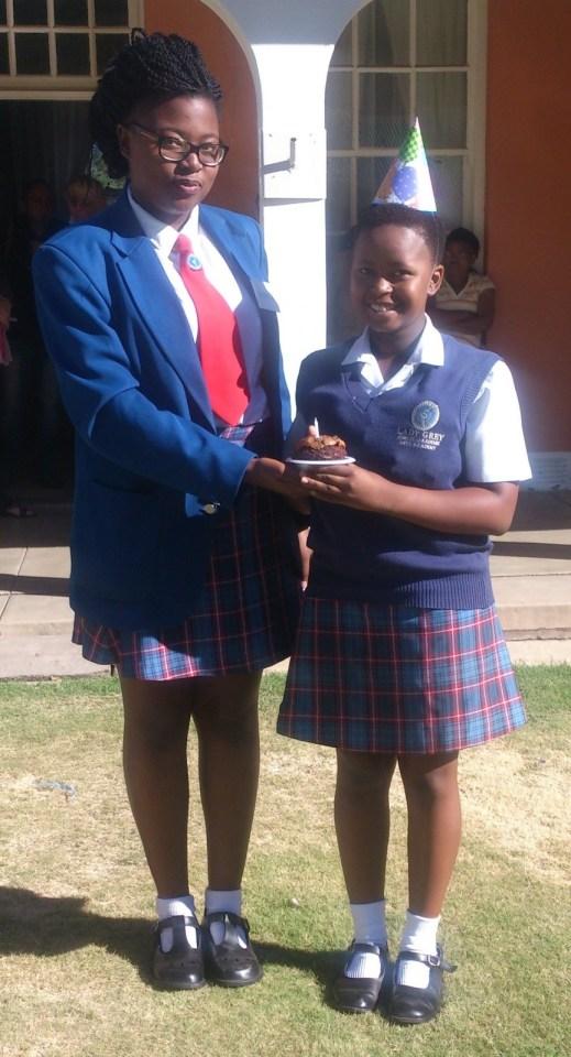 Leerlingraadslid, Yanga Mati oorhandig 'n spesiale koek aan Buhle Maloyi wat ook haar verjaarsdag op 8 Februarie vier.