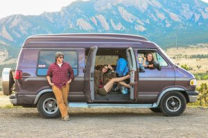 Band of Lovers in their van with mountains in the distance