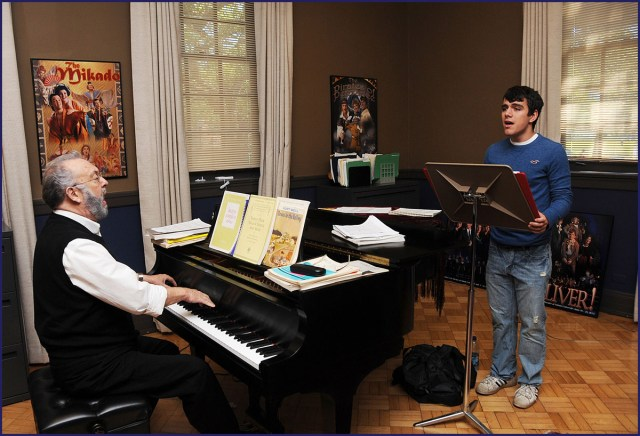 A college voice student sings as his teacher plays the piano