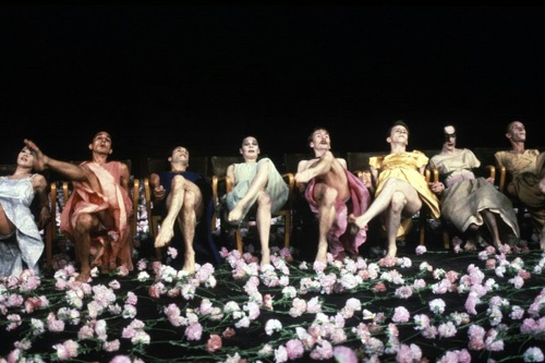 Members of Tanztheater Wuppertal in Nelken (Carnations). Dominique Mercy in pink, Lutz Forster in yellow, Kyomi Ichida far left. Courtesy Icarus Films