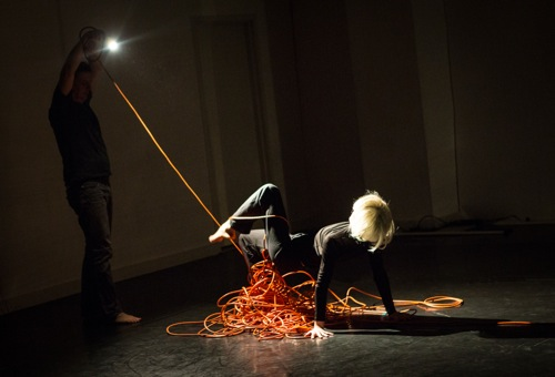 In the dark at left, Roderick Murray aims his light at Kimberly Bartosik. Photo: Yi-Chun Wu