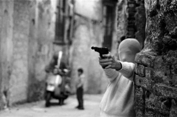 Bambino mascherato che impugna una pistola in una fotografia di Letizia Battaglia