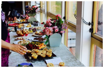Image contains a picture of a long table containing different snacks and finger food like small pies, fruits, and pastries. A pot full of flowers is also situated behind the food as decoration.