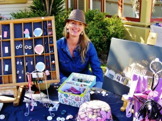 Image shows a stallholder wearing a fedora, showing her display of accessories and artisan pieces.
