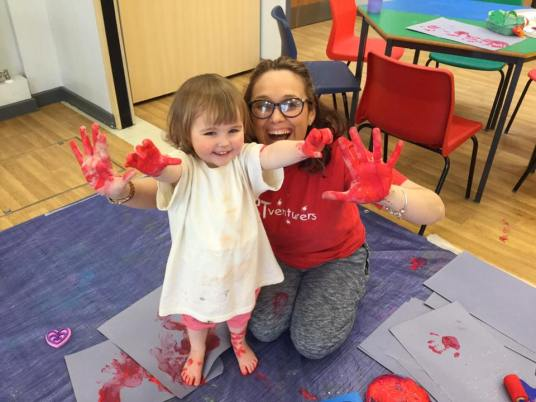 Toddler and adult enjoying painting