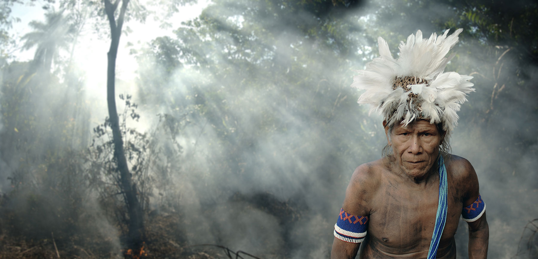 indigenous man in smokey forest