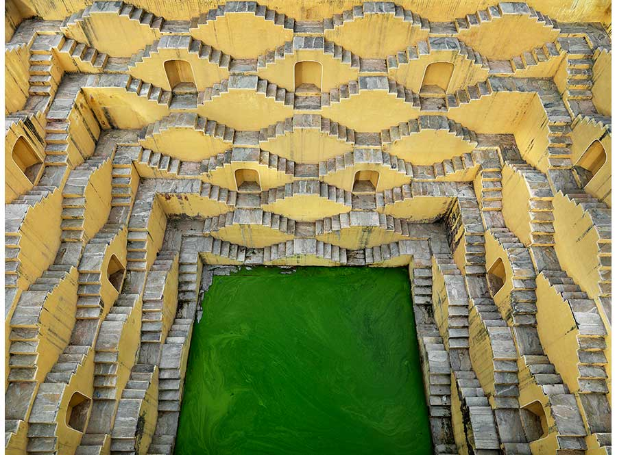 concrete stepwell structure with green pool
