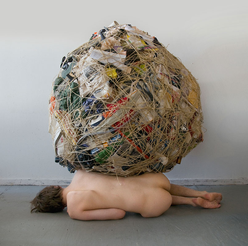 ball of possessions sitting on top of nude woman