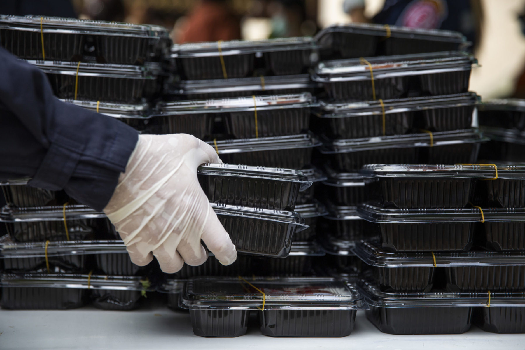 A gloved hand adds a prepared meal to a stack of plastic meal constainers.