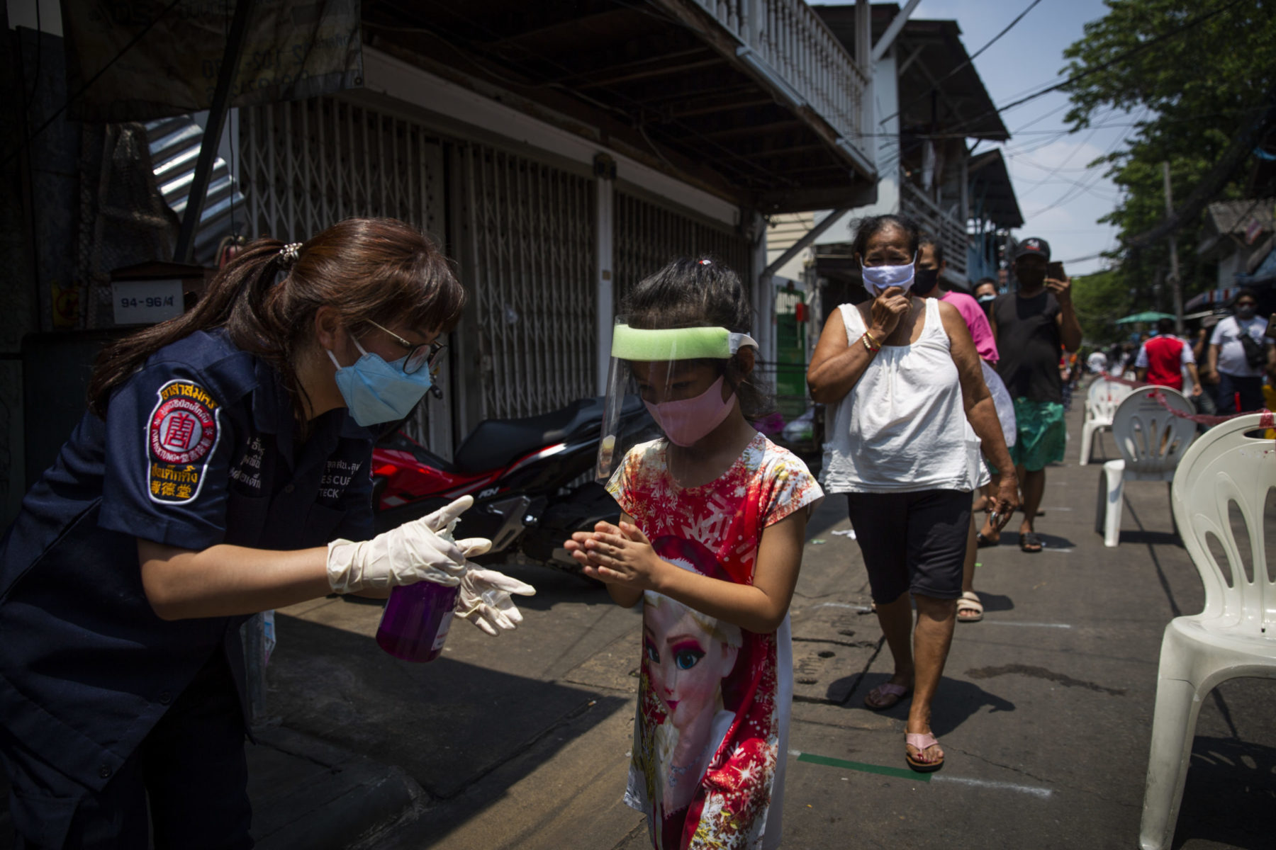 A young child wearing a mask and face shield accepts supplies from volunteer rescue staff.