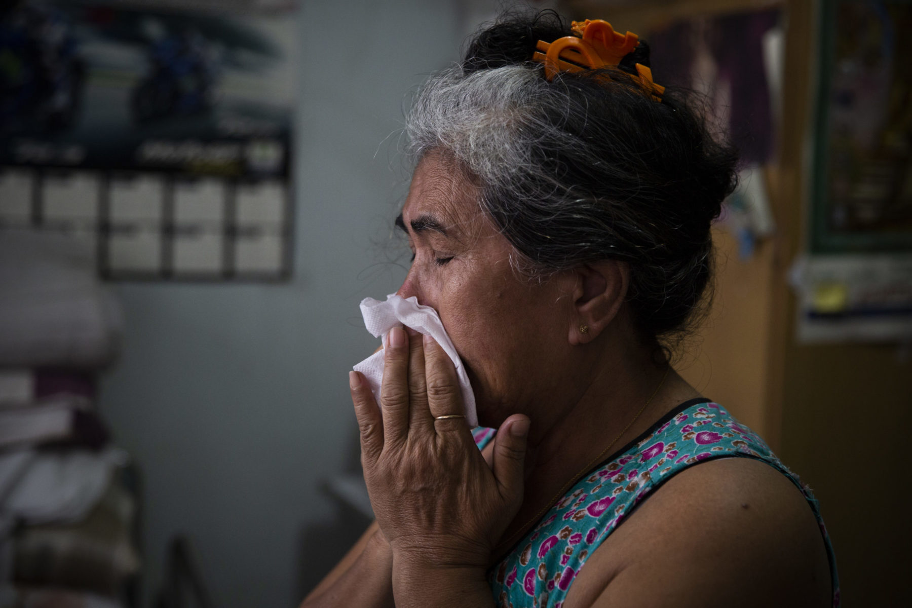 An emotional mother holds a tissue to her face in her home.