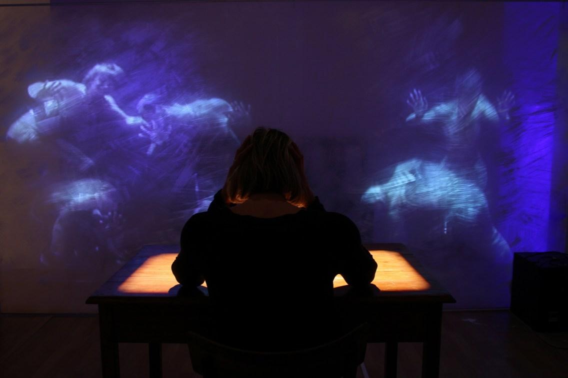 L'istituzione chiusa. Videoproiezioni sul tavolo bianco raccontano la storia dell'ospedale psichiatrico fino alla sua chiusura Courtesy Studio Azzurro