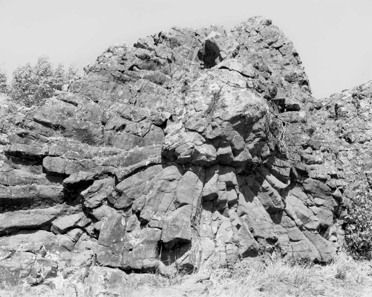 'Su carongiu de fanari' An andesitic mega pillow situated near the little town of Masullas, in the miocenic hills south of Monte Arci. It develops approximately along a 12 meters front and shows a pronounced radial cracking on the east side that gives it a characteristic rose window shape. The west side shows the globular structure of the single pillows. , 2016 From the series An investigation of the laws observable in the composition, dissolution, and restoration of land © Fabio Barile