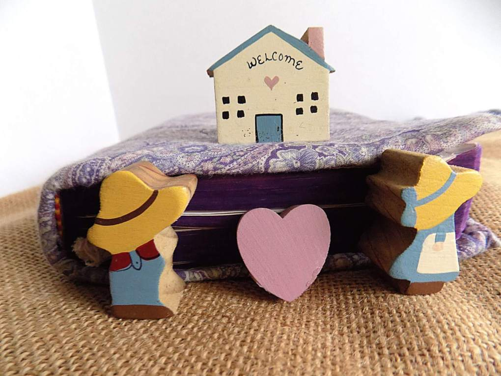 Tiny painted wooden figures of a boy and a girl with a heart between them in front of a Bible, and a little wooden house is on the Bible behind them.