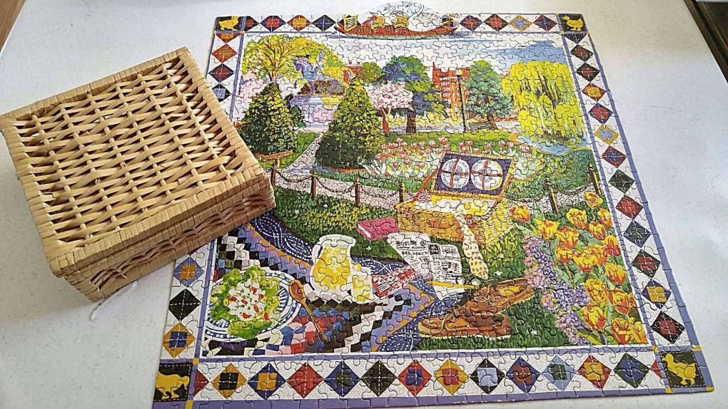 Puzzle with a picture of a picnic in the Boston park and a picnic basket that the puzzle goes in
