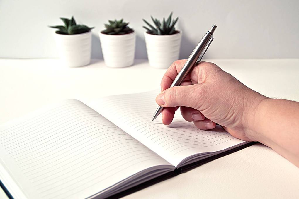 Hand writing in notebook to work on future planning