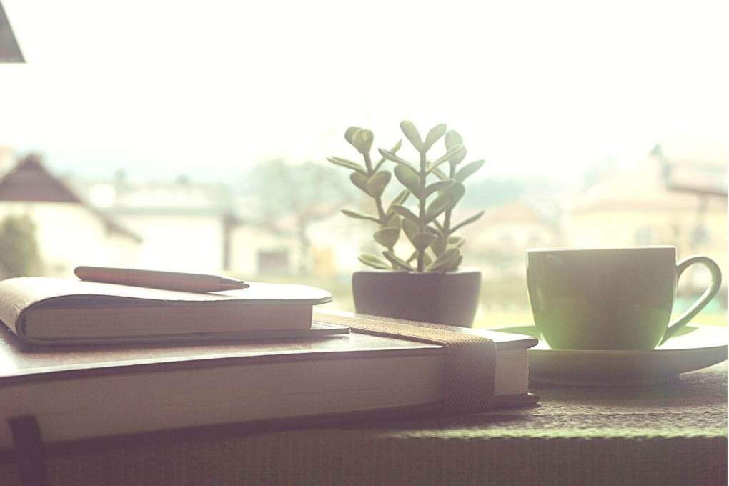 Notebooks and coffee on ledge overlooking houses