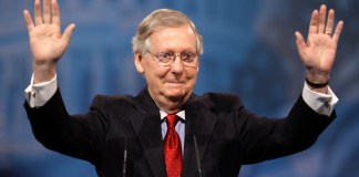Senator Mitch MConnell with hands up in the air smiling