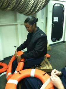 Thereasa Black preparing life rings so that they can be seen in the water in the event of a man overboard.