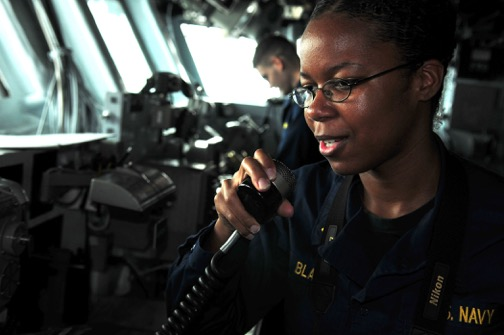 Ensign Thereasa Black makes an announcement from the bridge of an amphibious assault ship.