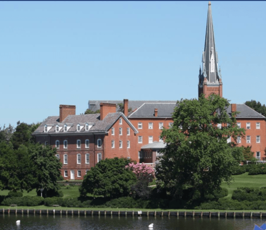 A old brick church building from across a creek. There is a pointy steeple.