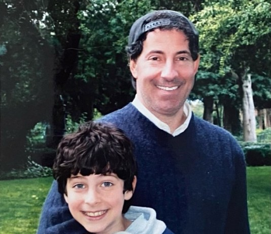 Adult man - father has arm around son. both are smiling.