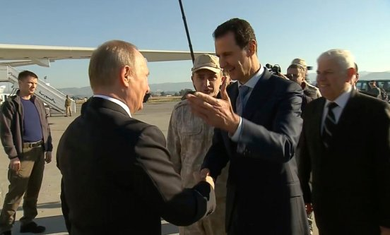 In this Monday, Dec. 11, 2017 frame grab made available by Russian Presidential TV Syrian President Bashar Assad, right, greets Russian President Vladimir Putin upon his arrival to the Hemeimeem air base in Syria. Declaring a victory in Syria, Putin on Monday visited a Russian military air base in the country and announced a partial pullout of Russian forces from the Mideast nation. Syrian President Bashar Assad is 4th at left. (Presidential TV photo via AP)