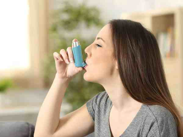 Side view of an asthmatic woman using an inhaler sitting on a couch in the living room at home