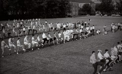 Dressed in their street clothes, band members practice in a field on campus.