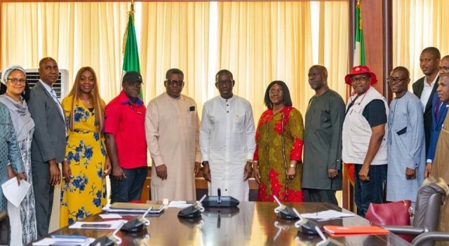 Governor Okowa flanked by the Replacement Campaign and Other Malaria Interventions Team, in Government House Asaba.