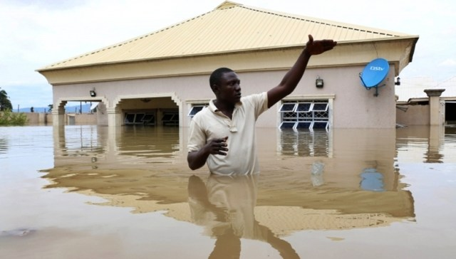 A Man Standing in a Flood Ravaged Compound