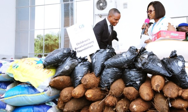 The wife of the Governor of Delta State and founder O5 Initiative, Dame Edith Okowa (right) presenting food items to Pastor Emmanuel Oletu, Proprietor Children Revolutionary Foundation, Irri, Isoko South Local Government Area during the 2019 World Orphans day celebration held in Asaba.