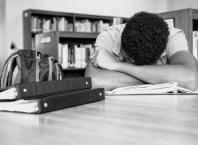 African American student overwhelmed with homework. pixelheadphoto/iStock