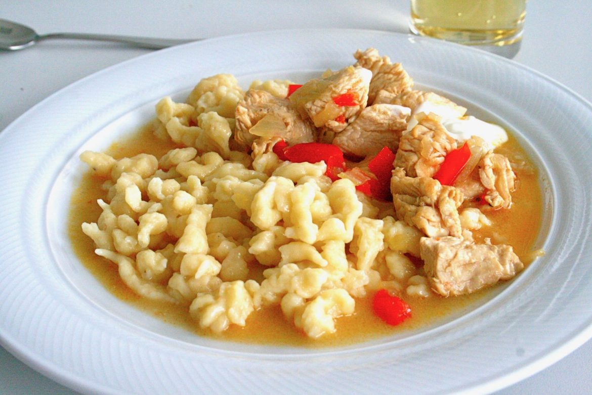 Chicken and pepper stew with Knöpfle on a white plate