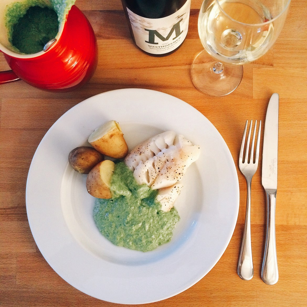 Wine bottle, glass, a jug and a plate of white fish with Grüne Soße and potatoes
