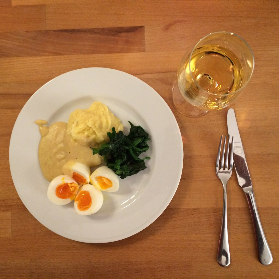A plate of eggs with mashed potatoes, mustard sauce, wilted spinach and a glass of wine