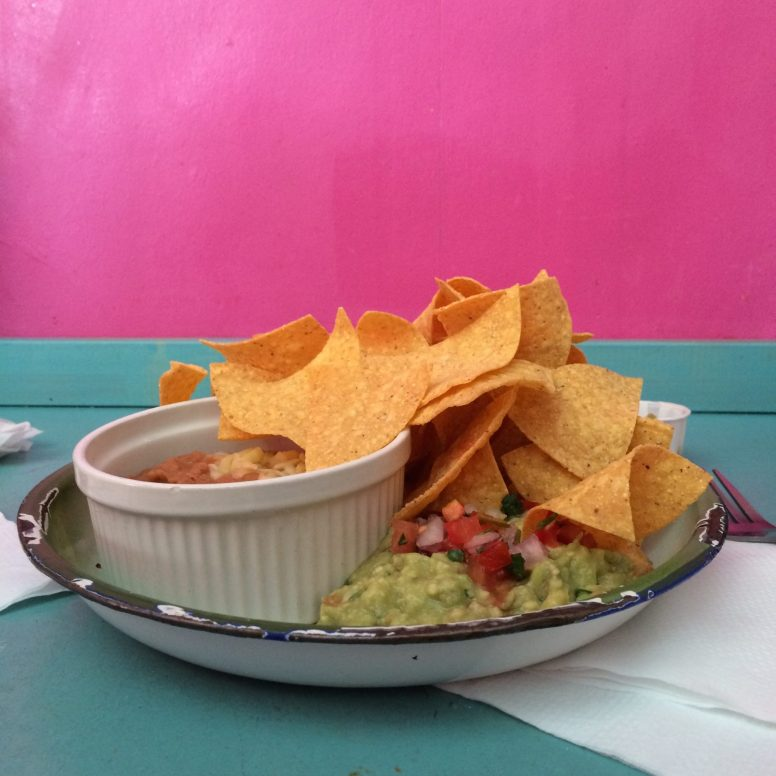 A tin plate of corn chips and guacamole