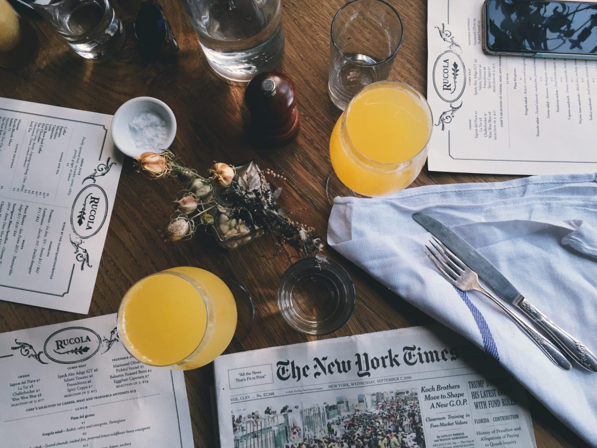 Flatlay of newspapers, menus and drinks