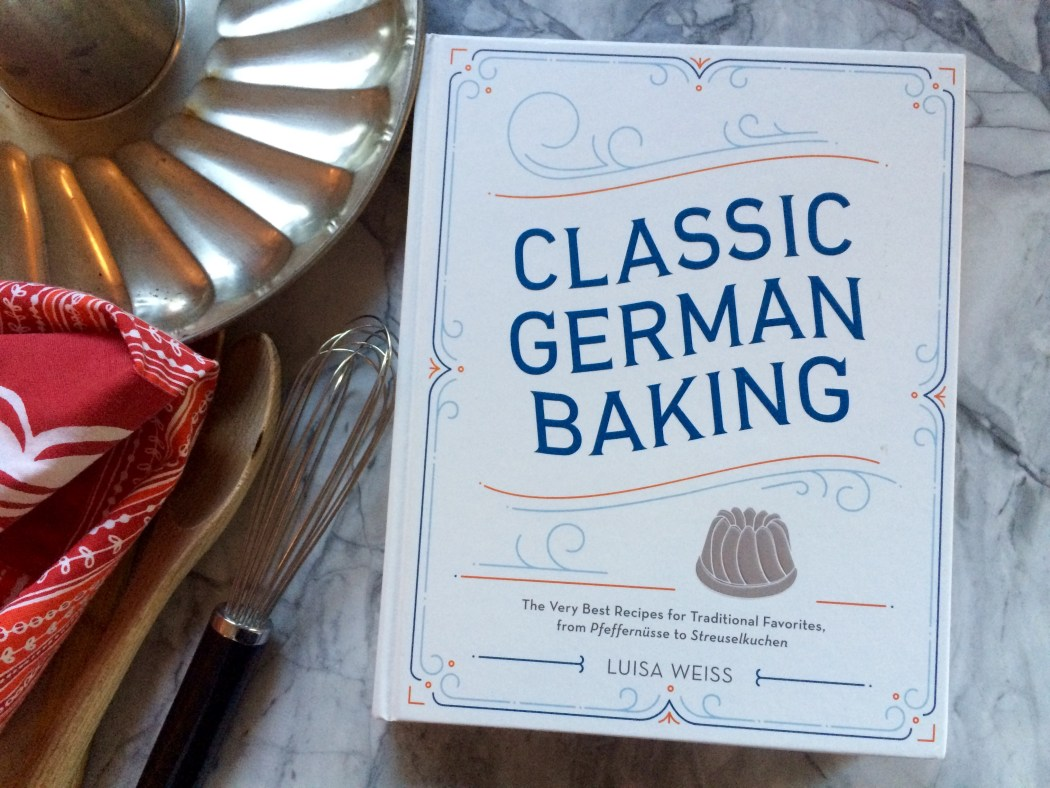 A copy of Classic German Baking by Luisa Weiss on a marble table alongiside baking tools