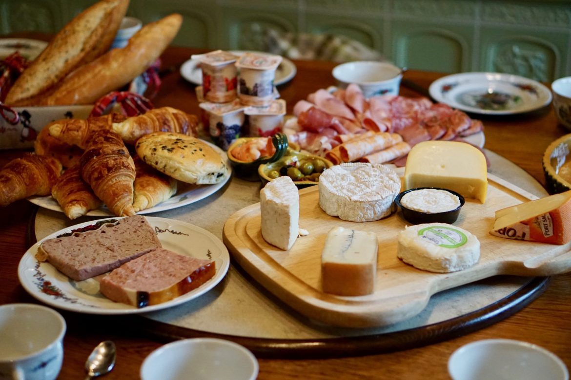 A breakfast spread of cheeses, meats, croissants and yoghurts