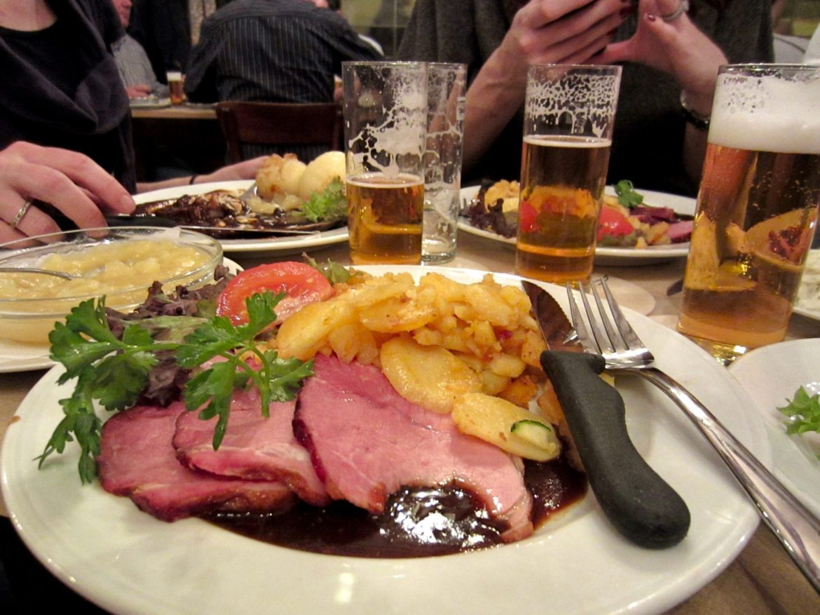 A plate of Krustenbraten with Bratkartoffen and glasses of German beer (Kölsch)