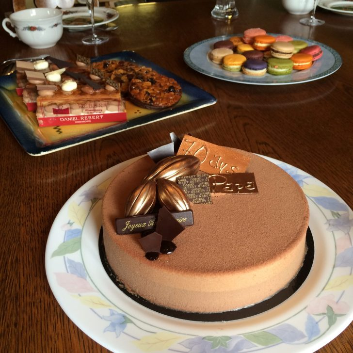 French Patisserie cake, slices and colourful macarons on a table