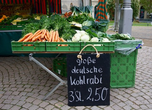 A market stall in Germany with a chalkboard advertising kohlrabi