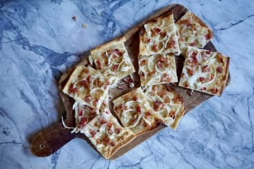 Alsace-style Flammkuchen on a wooden board and a marble table