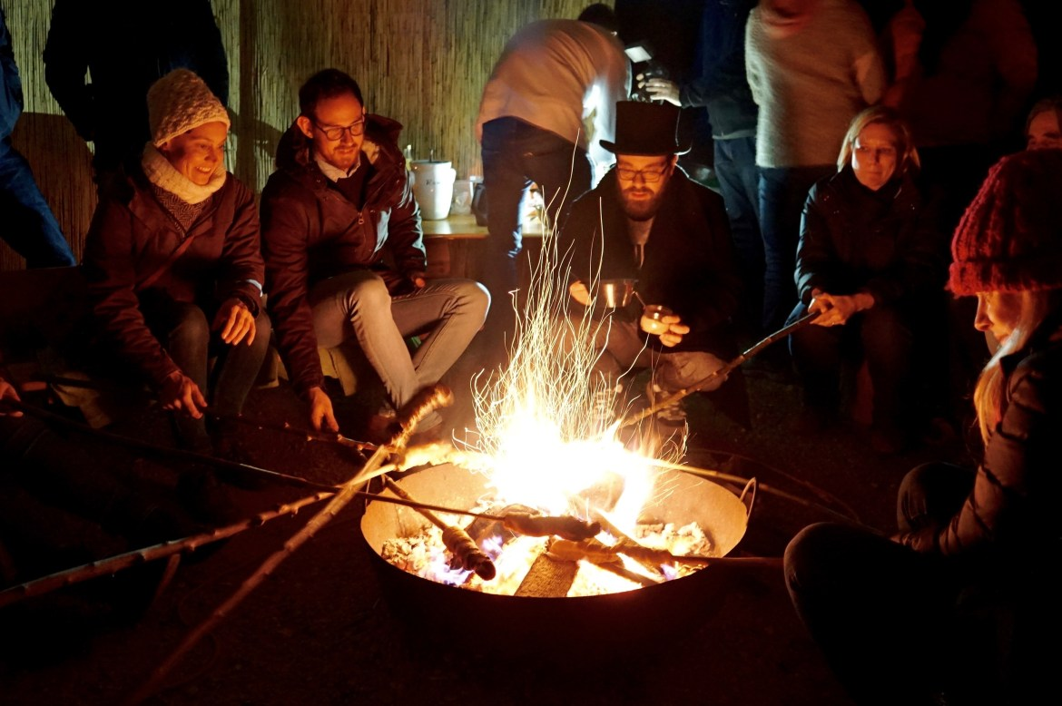 A group of Germans sitting around a fire baking bread on sticks