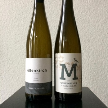 Two bottles of white German wine sitting on a black tray