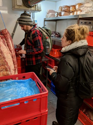 A man and a woman in a cold room at a butcher's shop looking at hanging meat