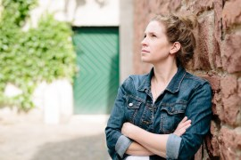 Portrait of Christie Dietz leaning against a brick wall